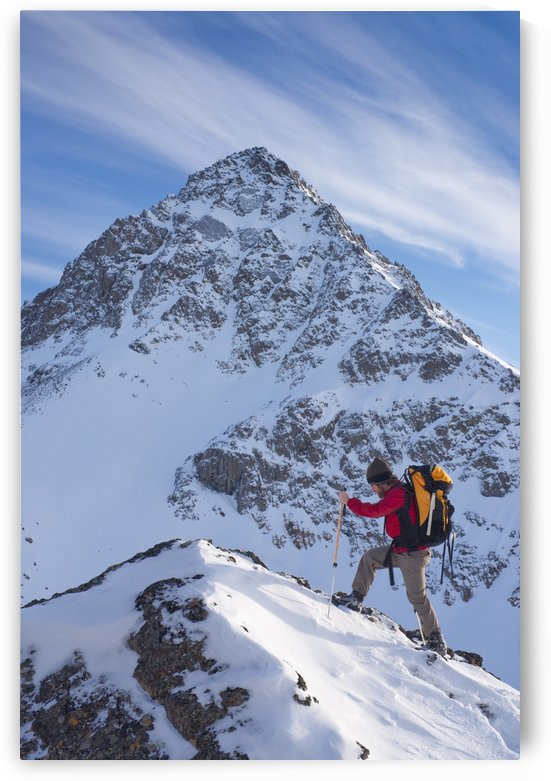 Man With Backpack Hiking On A Snow Covered Ridge Below Ptarmigan Peak In Chugach State Park, Southcentral Alaska, Winter by PacificStock