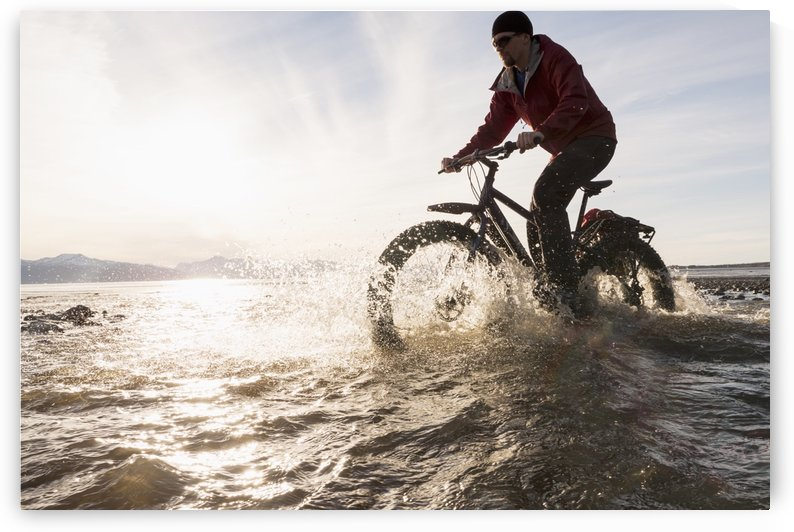 Bicyclist riding his fat bike across a tidal stream along Kachemak Bay, Homer, Kenai Peninsula, Southcentral Alaska, winter by PacificStock