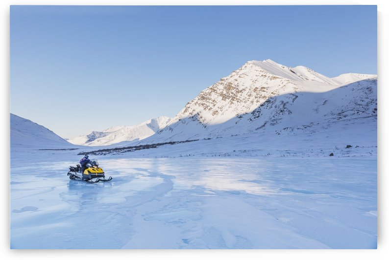 Native youth riding Snowmachine on overflow ice, Inukpasugruk (Giant) Creek, Anaktuvuk Pass, Gates of the Arctic National Park, Brooks Range, Northern Alaska, USA. by PacificStock