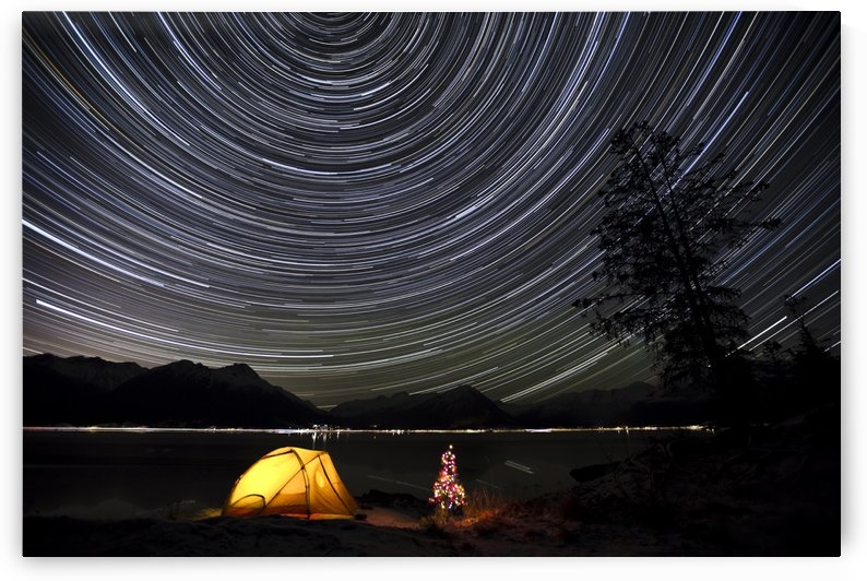Star trails circle above the Chugach Mountains with a backpacking tent and Christmas Tree along the shore of Turnagain Arm, Southcentral, Alaska, Winter by PacificStock