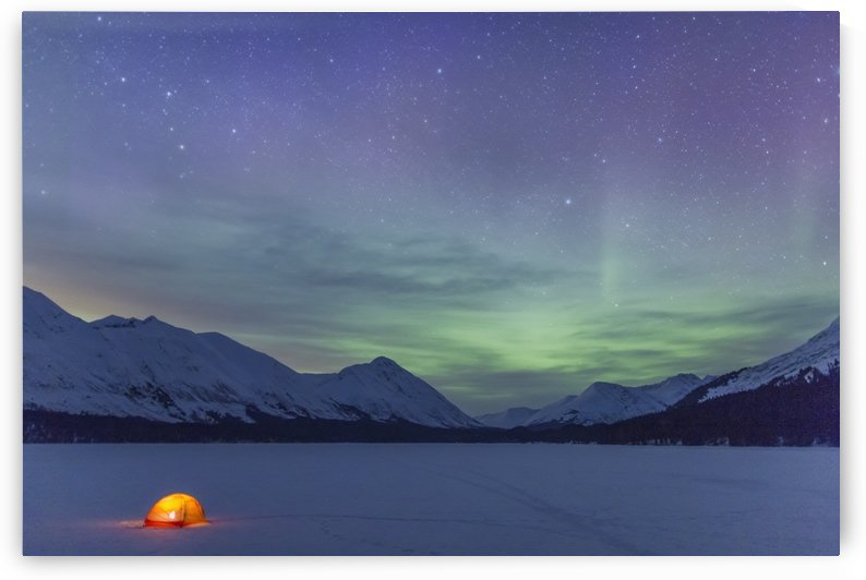 Nighttime view of a lit tent on a snow covered Trail Lake with the moon, stars, and Northern Lights overhead, Moose Pass, Kenai Peninsula, Southcentral Alaska by PacificStock