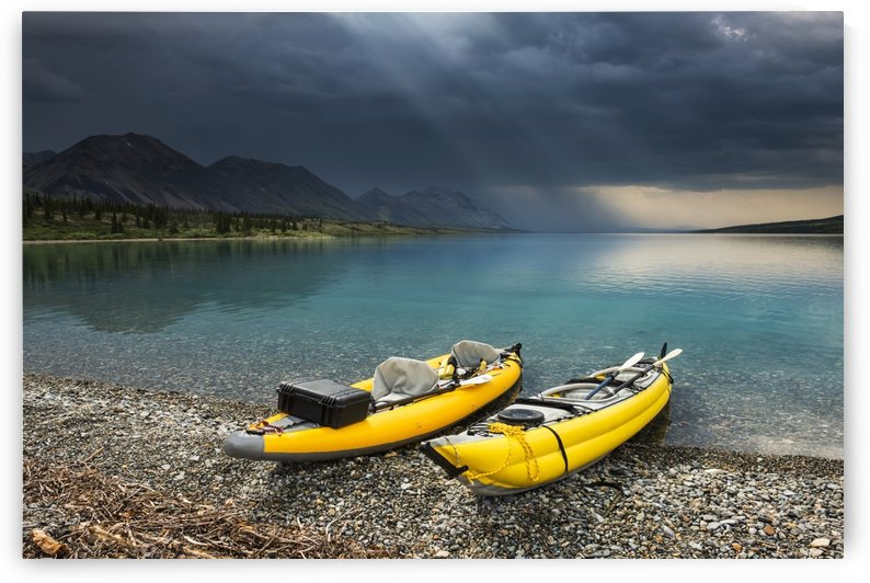 A pair of yellow inflatable kayaks on the Lower Twin Lake beach with a summer thunderstorm in the background, Lake Clark National Park & Preserve, Southcentral Alaska. by PacificStock
