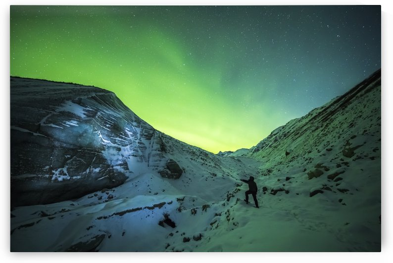 A man lights up the ice of Castner Glacier with a flashlight underneath a diffuse aurora display; Alaska, United States of America by PacificStock