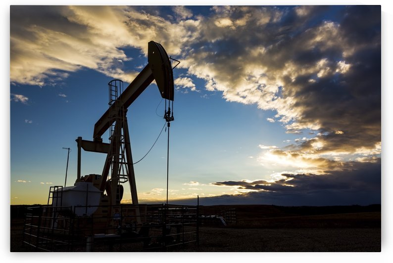 Silhouette of pump jack with dramatic storm clouds and blue sky; Alberta, Canada by PacificStock