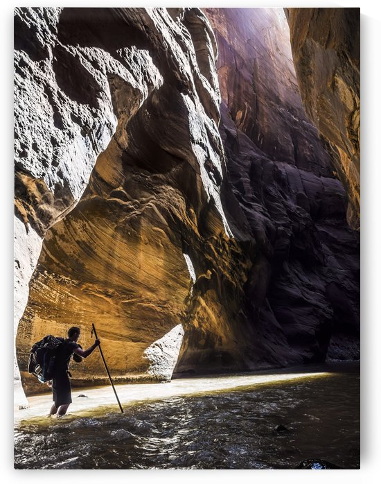 A hiker makes his way over the rocky river bottom of the Virgin River Narrows, a majestic portion of one of America's most famous national treasures, Zion National Park; Utah, United States of America by PacificStock