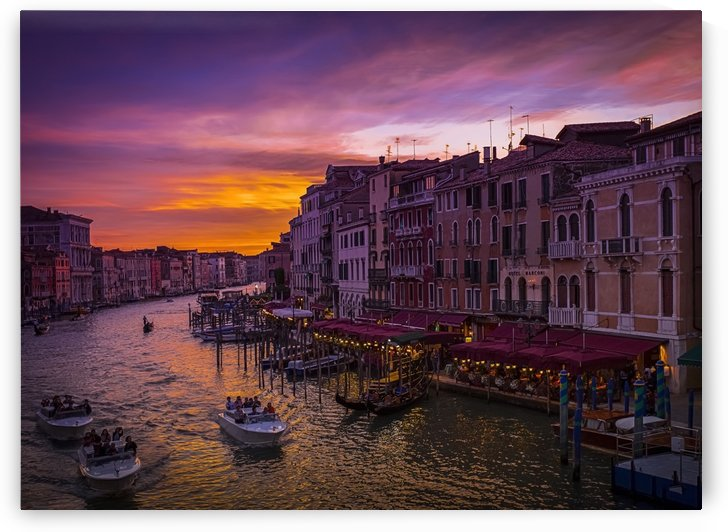 A dramatic and colourful sunset over the canal and buildings, with water taxis in the canal; Venice, Italy by PacificStock