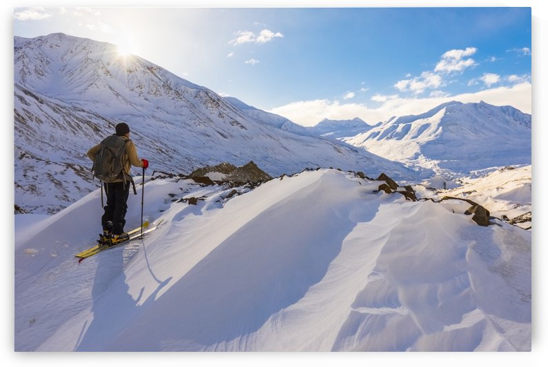 A backcountry skier looks over the Black Rapids Glacier valley from a high point on the terminal moraine in winter; Alaska, United States of America by PacificStock