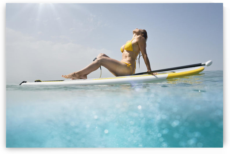 A woman in a yellow bikini sits with her paddle and board basking in the sunlight on the ocean;Tarifa cadiz andalusia spain by PacificStock