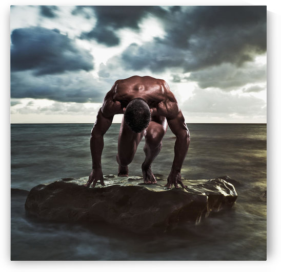 A muscular man in the starting position on a wet rock in the water;Tarifa cadiz andalusia spain by PacificStock