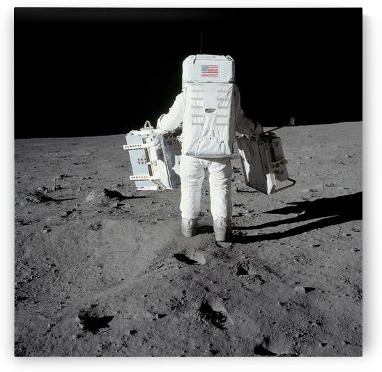 Astronaut carrying equipment to the deployment site on the moon. by StocktrekImages