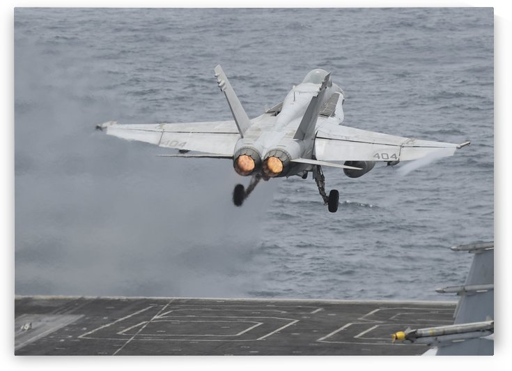 An F-A-18C Hornet launches from the flight deck of USS Nimitz. by StocktrekImages