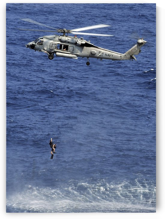 Search and rescue swimmers being hoisted into a helicopter. by StocktrekImages