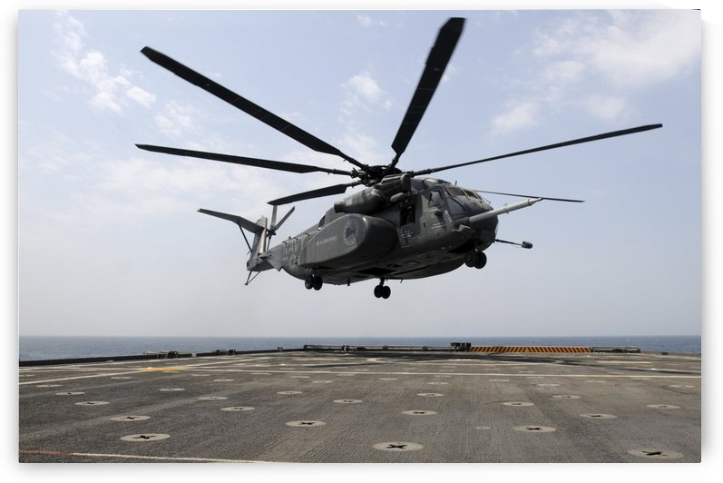 An MH-53E Sea Dragon prepares to land on the flight deck aboard USS Ponce. by StocktrekImages