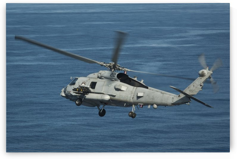 An MH-60R Sea Hawk maneuvers over the South China Sea. by StocktrekImages