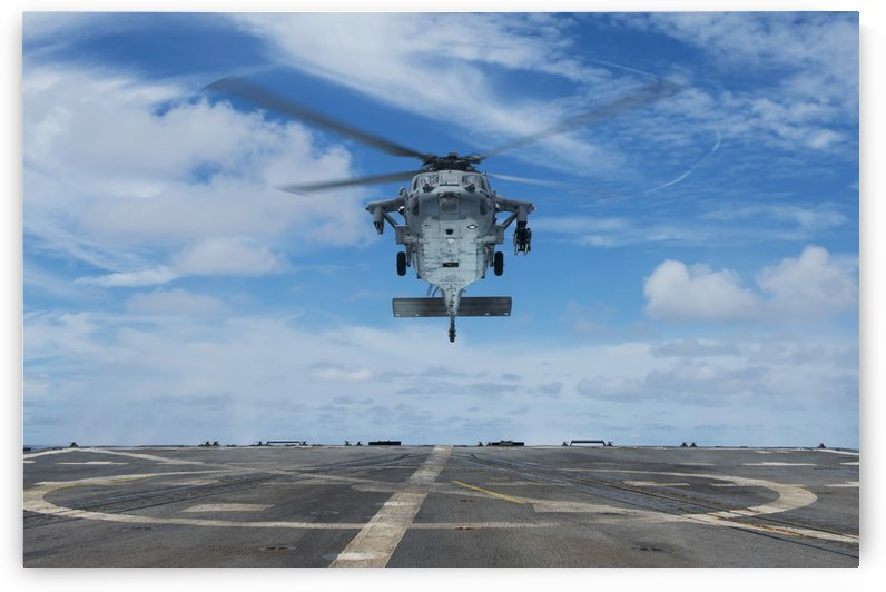 A U.S. Navy MH-60S Seahawk helicopter prepares to land. by StocktrekImages