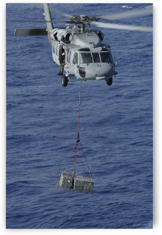 An MH-60S Knighthawk transports supplies during a replenishment at sea. by StocktrekImages