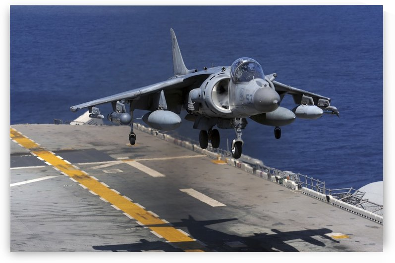 An AV-8B Harrier jet lands on the flight deck of USS Essex. by StocktrekImages