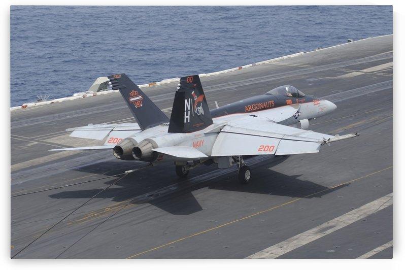 An F-A-18E Super Hornet lands on the flight deck of USS Nimitz. by StocktrekImages