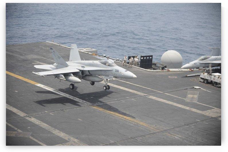 An F-A-18C Hornet lands on the flight deck of USS Nimitz. by StocktrekImages