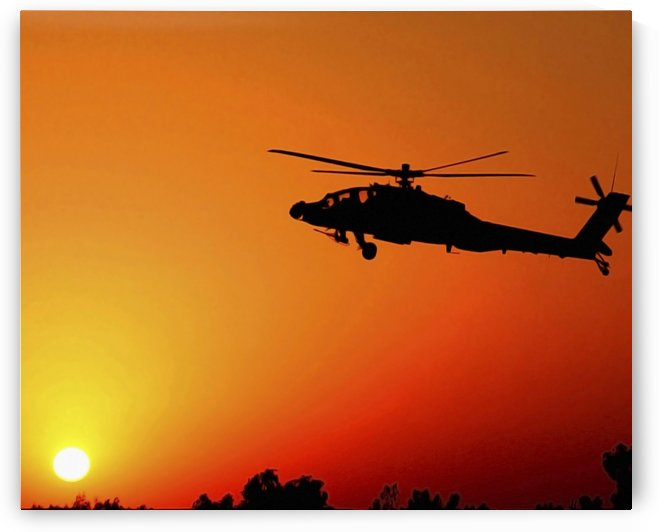 A U.S. Army AH-64 Apache Helicopter prepares to land as the sun comes up. by StocktrekImages