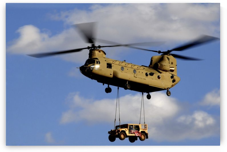 A U.S. Army CH-47 Chinook helicopter transports a Humvee. by StocktrekImages