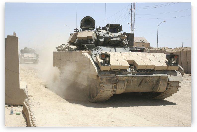 An M2 Bradley Fighting Vehicle patrols past Command Post Hit Iraq. by StocktrekImages