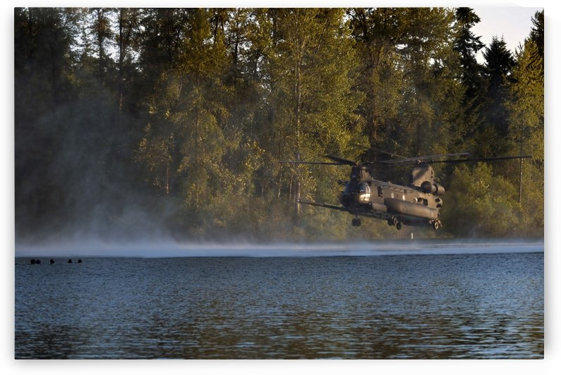 Airmen wait in a lake for an MH-47 Chinook helicopter to extract them. by StocktrekImages