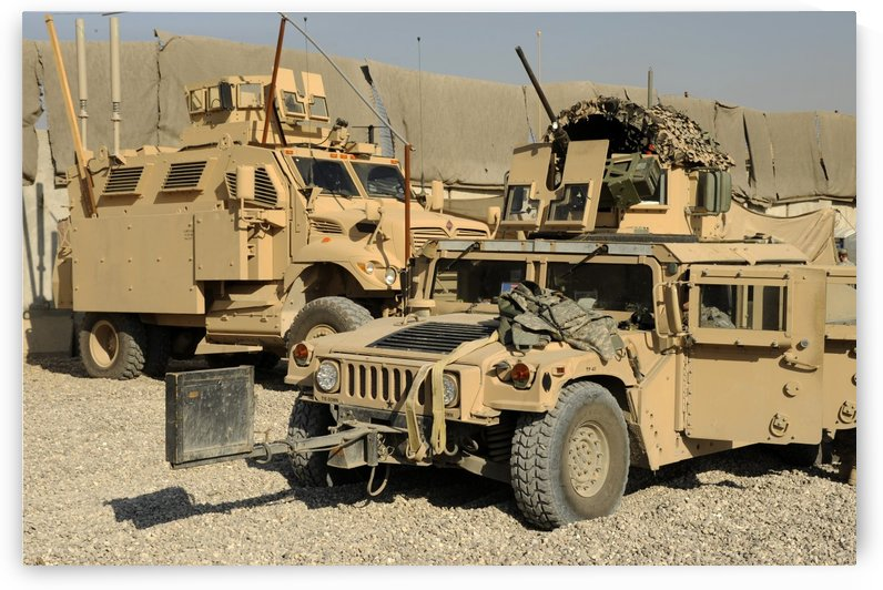 A M1114 humvee sits parked in front of a MaxxPro MRAP. by StocktrekImages