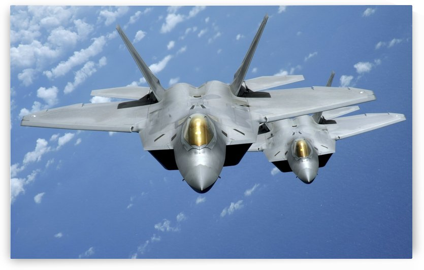 Two F-22 Raptors fly over the Pacific Ocean. by StocktrekImages