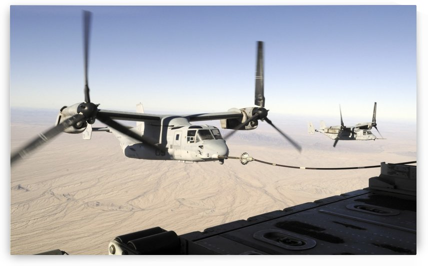 A MV-22 Osprey refuels midflight while another waits its turn. by StocktrekImages