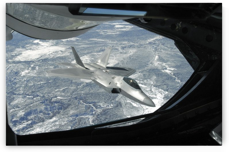 An F-22 Raptor banks away from a KC-135 Statotanker during a refueling operation. by StocktrekImages