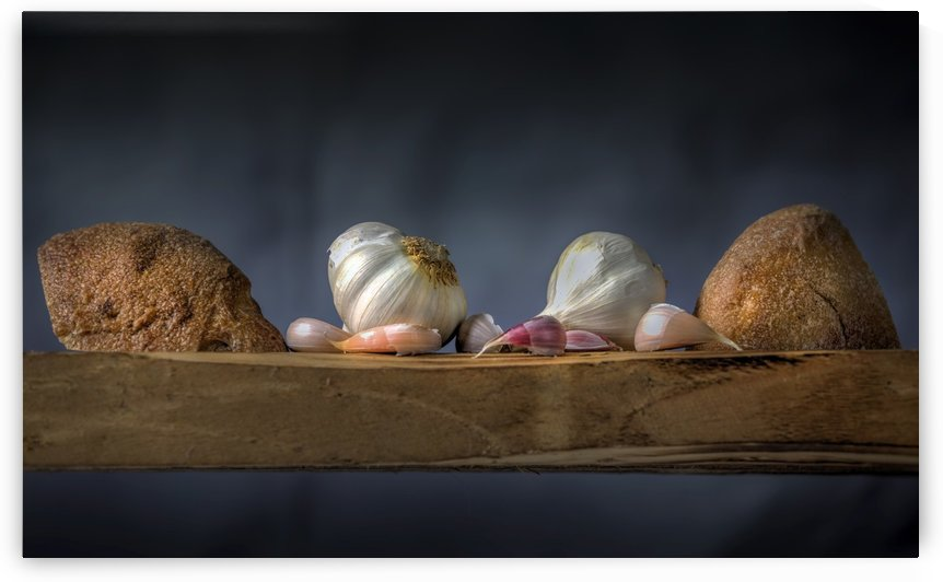 Garlic cloves and bread rolls by Leighton Collins