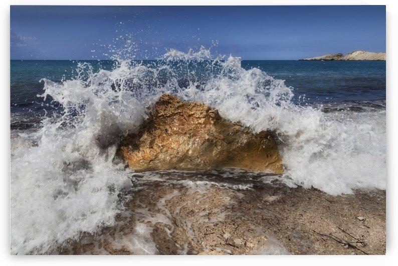 Crashing wave on a Greek beach by Leighton Collins