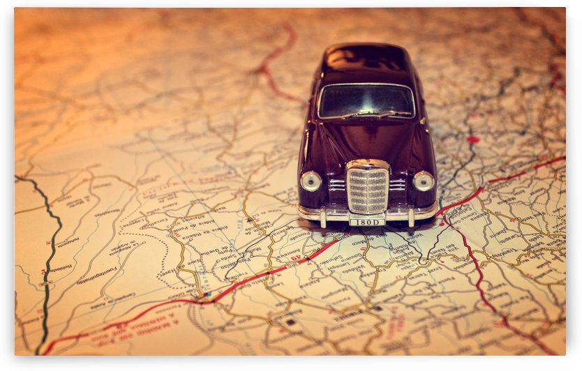 Hit the road - Travel concept with vintage miniature car on road map by Alex Pell