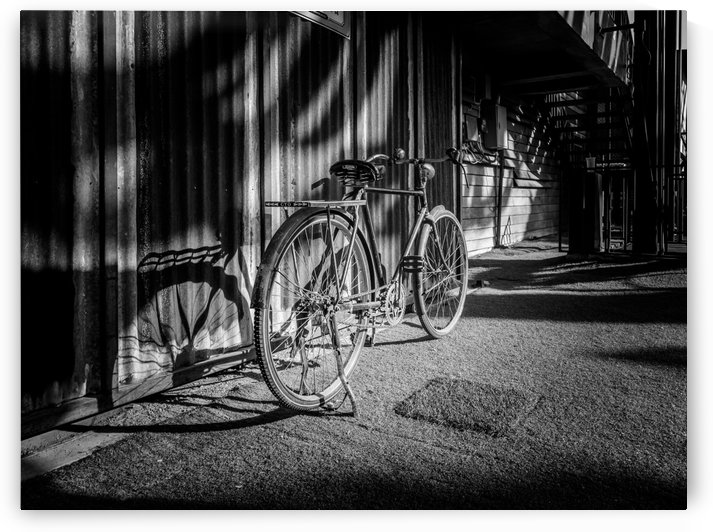 Bicycle parked against the building black and white by RezieMart