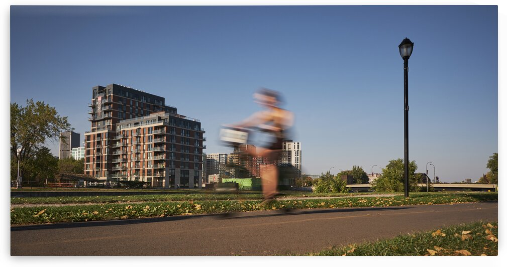 Bike rider cycling in downtown urban area Montreal Quebec Canada by Atelier Knox