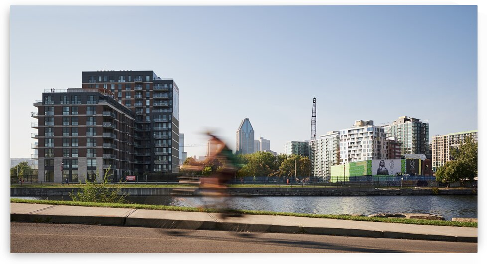 Bike rider cycling in downtown urban development area Montreal Quebec Canada by Atelier Knox