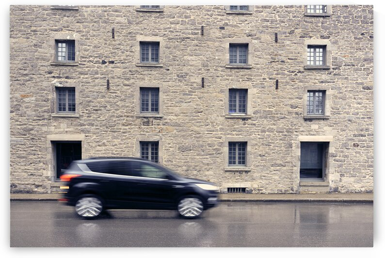 Abstract of car driving along road with stone walled building behind Montreal Quebec Canada by Atelier Knox