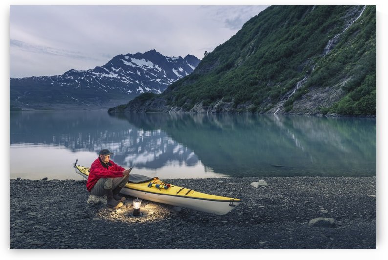 Man reading on a electronic tablet while camping with a kayak at Shoup Bay State Marine Park, Prince William sound, Valdez, Southcentral Alaska by PacificStock