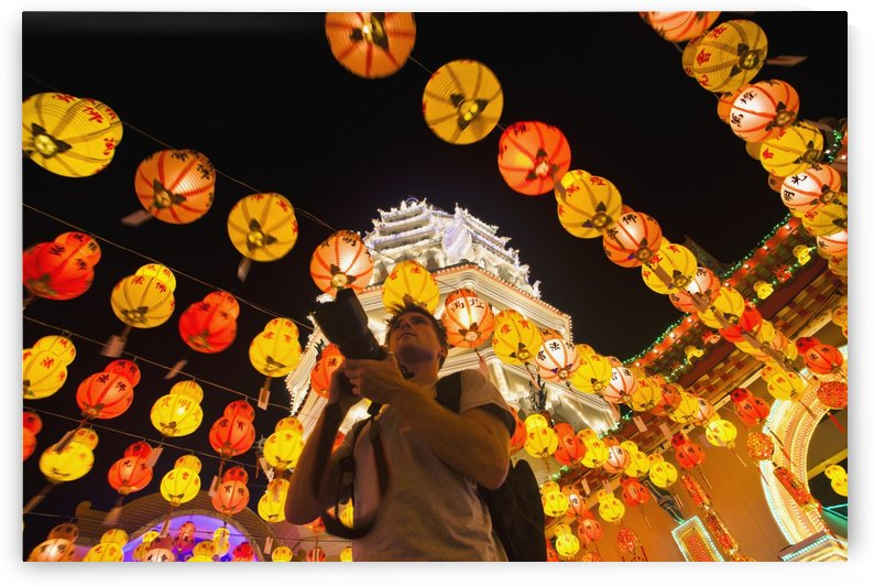 The fantastic lighting of Kek Lok Si Temple and a tourist with a camera; Penang, Malaysia by PacificStock