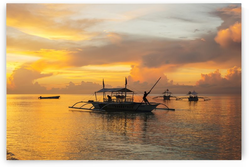 Beautiful sunrise in Alona Beach, a man moving his boat to reach the shore with a long stick; Panglao Island, Bohol, Philippines by PacificStock