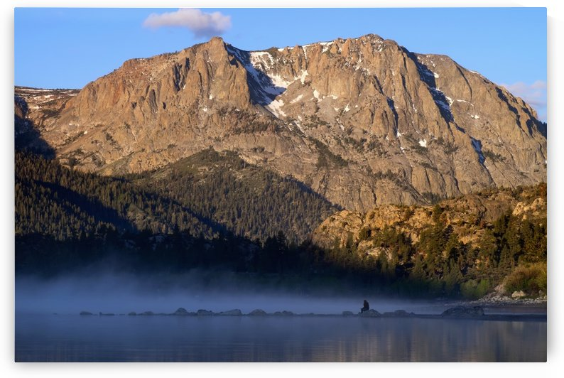 Woman sits on rock and views sunrise over June Lake, Mono Basin; California, United States of America by PacificStock