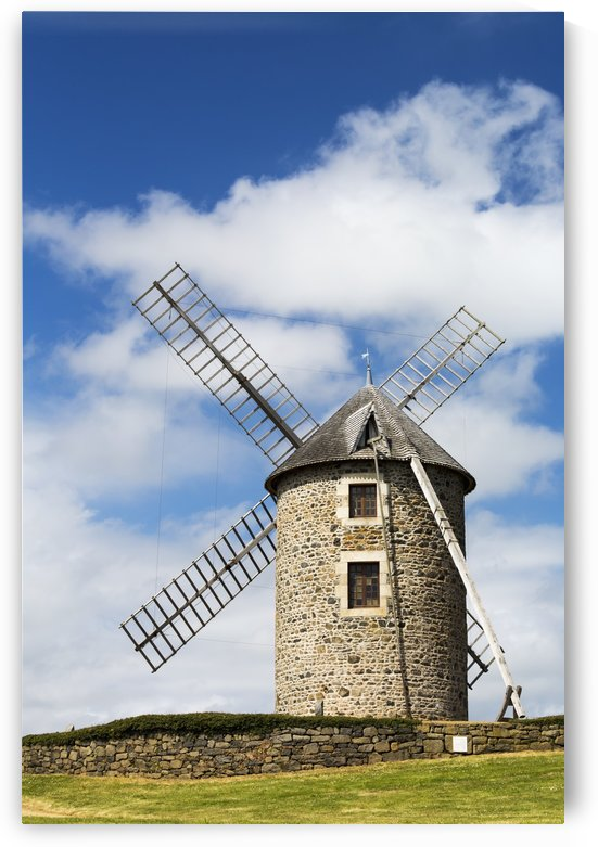 An old stone windmill on a hillside with wooden blades, surrounded by a stone fence with blue sky and clouds; Brehec, Brittany, France by PacificStock
