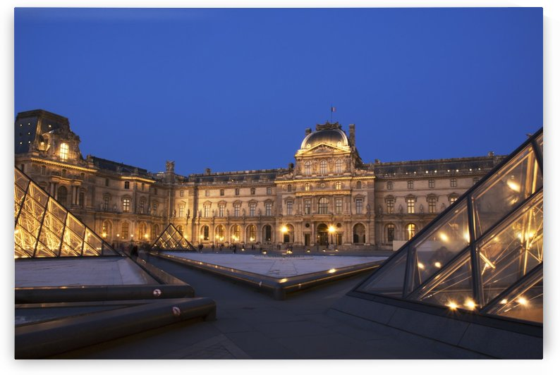 Le Louvre palace buildings and pyramids at night in golden light; Paris, France by PacificStock