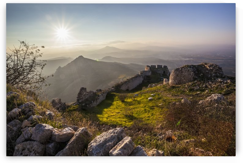 Ruins of a stone wall and buildings with a sunburst and mountains; Corinth, Greece by PacificStock