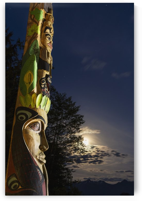 A large totem pole lit up at night in Sitka National Historic Park with the moon and clouds in the background; Sitka, Alaska, United States of America by PacificStock