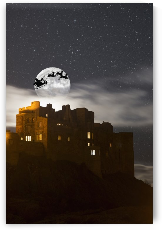 Santa in his sleigh and reindeer silhouetted in the starry sky in front of the moon over buildings; Bamburgh, Northumberland, England by PacificStock