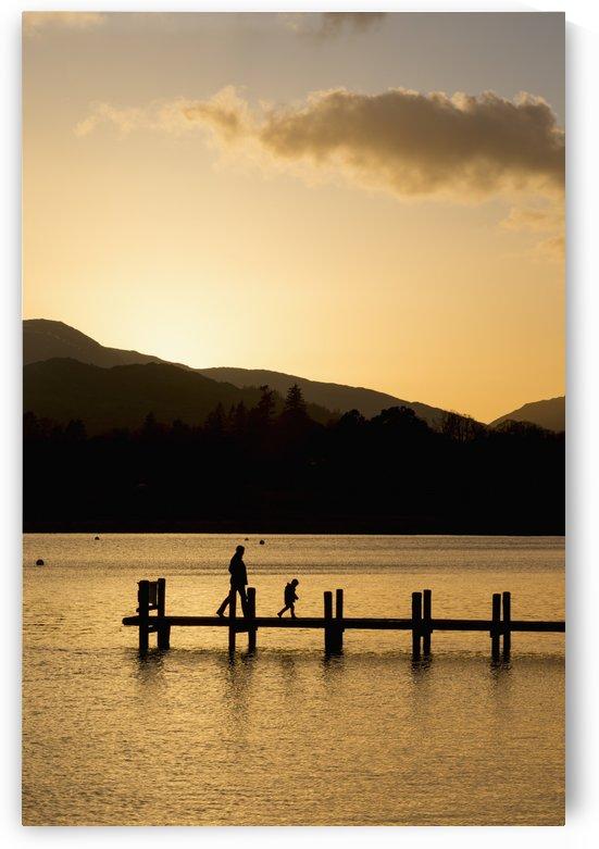 Silhouette of a parent and child walking on a dock on a tranquil lake at sunset; South Lakeland District, England by PacificStock