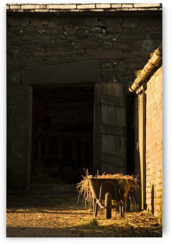 Wheelbarrow Beside A Barn by PacificStock