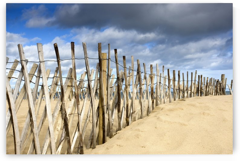 South Shields, Tyne And Wear, England; Dark Clouds Over Fence On A Beach by PacificStock